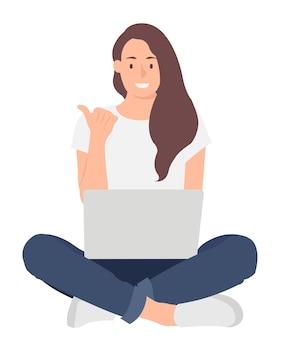 Женщина работает на ноутбуке, сидя на полу со скрещенными ногами
