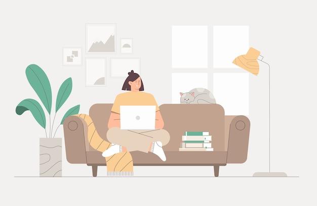 Женщина, работающая с ноутбуком на диване в уютной комнате