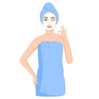 화장용 점토나 시트 마스크를 사용하여 수건으로 싸인 여자. 확인 제스처를 보여주는 윙크하는 여자.
