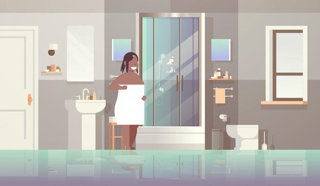 Женщина, обернутая белым полотенцем девушка стоит в ванной комнате после концепции душа современная квартира