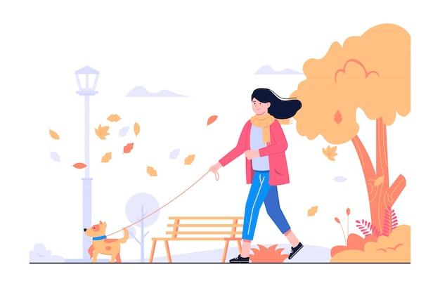 女性と秋の概念図を歩く犬