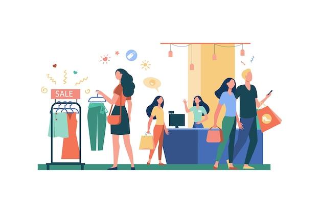 Donne che comprano vestiti nell'illustrazione piana di vettore isolata negozio di abbigliamento. ragazze dei cartoni animati e consumatori che scelgono capi di abbigliamento, indumenti o abiti moderni. negozio di moda e stile