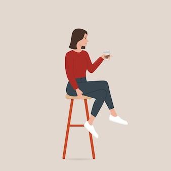 コーヒーを飲み、バースツールに座っている女性