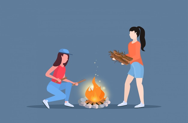 Women hikers making fire couple girls holding firewood for bonfire hiking camping concept travelers on hike horizontal full length flat