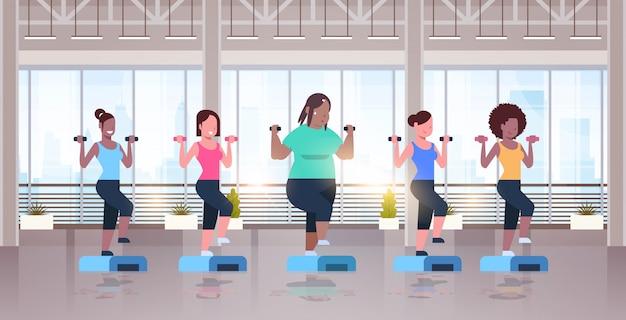 체육관에서 단계 플랫폼 다른 체형 여자 훈련에 웅크 리고 아령을 들고 여성
