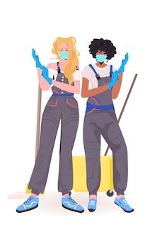 Женщины-дворники профессиональные уборщики офиса в медицинских масках в перчатках коронавирус карантин концепция вертикальный