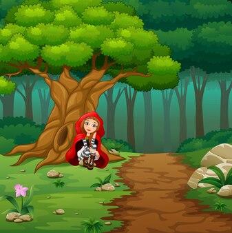 숲에서 여자 레드 후드 쪼 그리고 앉는