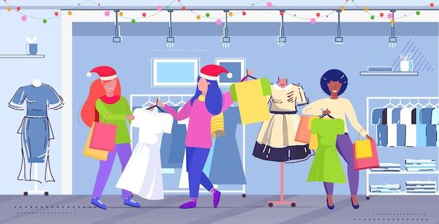 サンタ帽子の女性の買い物客が季節のショッピング販売の最後のドレスの顧客のカップルのために戦うコンセプトモダンファッションブティックインテリアフルレングス