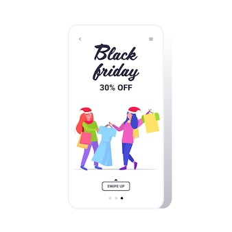 Women shoppers in santa hats fighting for last dress customers couple on seasonal shopping sale fight concept smartphone screen online mobile app full length