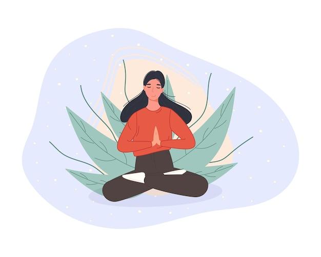 床に座って蓮華座で瞑想する女性