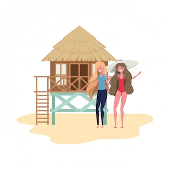 Women standing in the beach with beach house