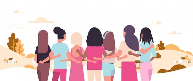 Women standing and embracing together mix race girls struggling against breast cancer disease awareness and prevention concep