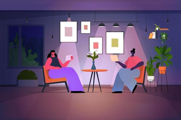Женщины, использующие ноутбук и планшетный пк в темной ночной гостиной, концепция онлайн-общения в сети социальных сетей