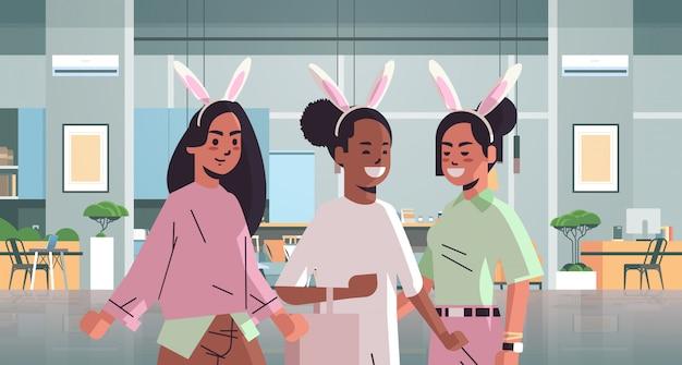 幸せなイースター休暇を祝うバニーの耳かわいいミックスレースの女の子を着ている女性