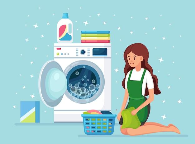 바구니, 더러운 옷을 가진 여자. 일상, 활동. 배경에 세제 d로 세탁기를 열었습니다. 가사 용 전자 세탁 장비로 주부 세척