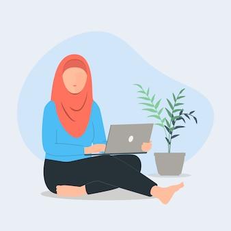 ヒジャーブが床に座っている女性。在宅勤務のコンセプト