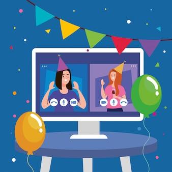 テーブルの上のコンピューターでパーティーハットを持つ女性