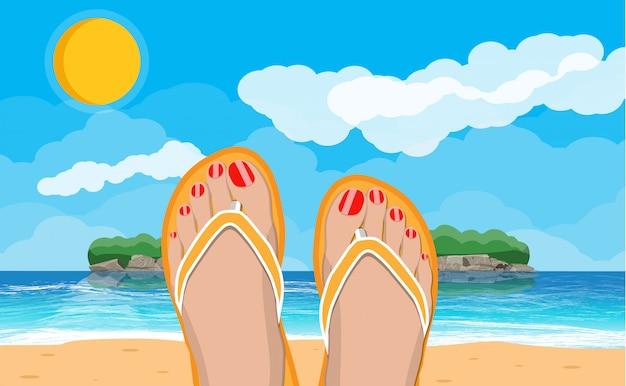 Womens feet in flip flops. landscape of beach