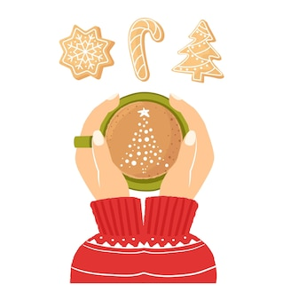 一杯のコーヒーを保持している女性の手上面図クリスマス生姜クッキー