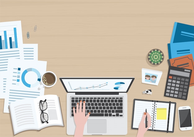 Деревянный стол сверху, руки женщины работают на ноутбуке и канцелярских принадлежностях