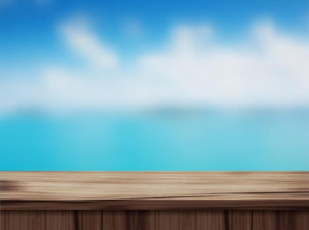 나무 테이블 상단과 흐린 된 해변.