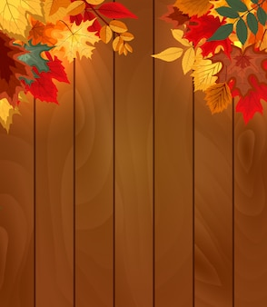 Wooden background with falling autumn leaves