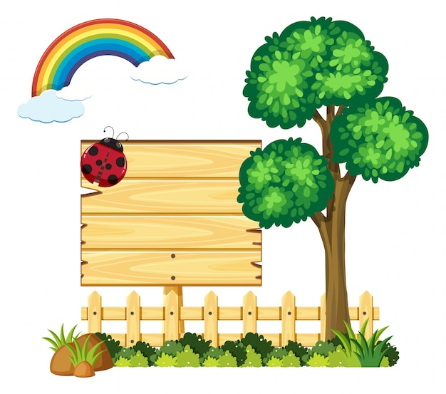 Wooden board in garden with tree and rainbow