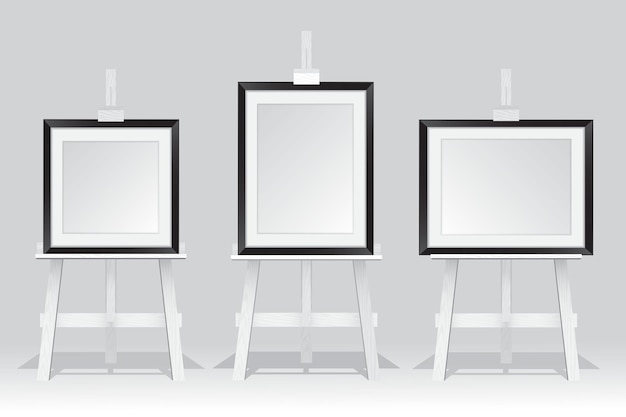 Wooden easel stand with picture frame on white background