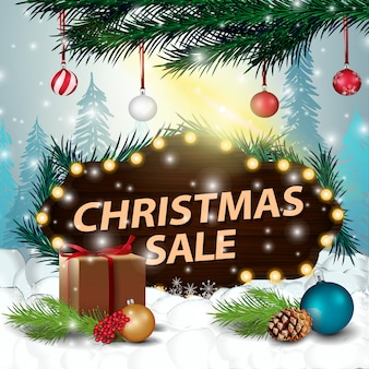 A wooden sign at a discount in the snowdrift with gifts