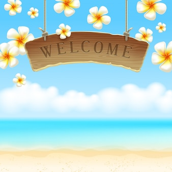 The wooden signboard welcome - hangs against a tropical flowers and sea shore