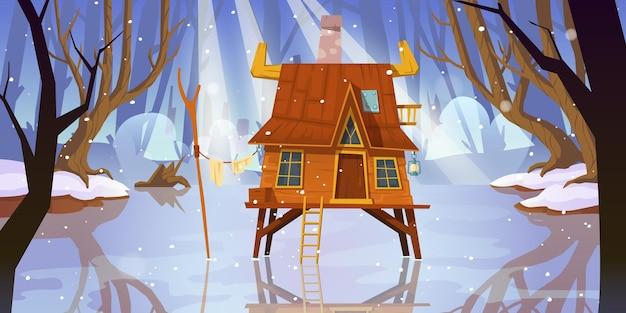 Casa su palafitte in legno a palude congelata nella foresta invernale