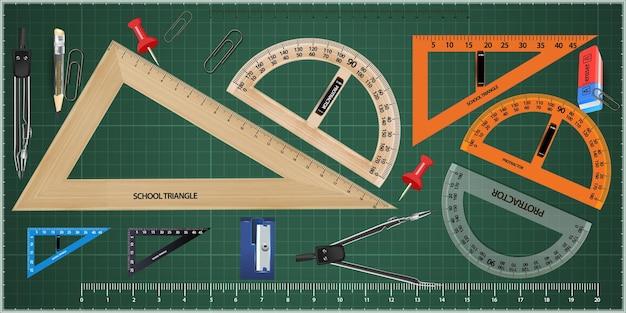 緑に分離された木製の三角形と定規。測定ツールのセット: 定規、三角形、分度器。