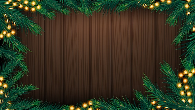 Wooden wall with frame made of christmas tree branches and garland. wooden christmas background