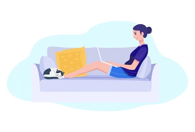 Работа из дома концепции, молодая женщина, сидя на диване и работает на ноутбуке.