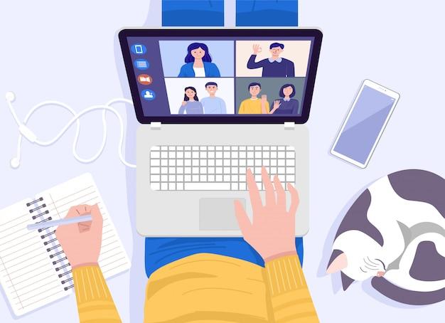 ホームコンセプトから動作します。床に座って、自宅でビデオ会議用のラップトップを使用している若い男の平面図です。
