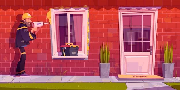 Рабочий устанавливает пластиковое окно в доме