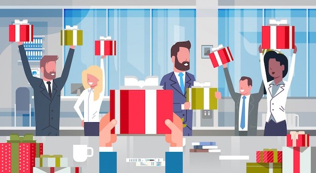 Workers bonus concept cheerful business people team holding red gift boxes in modern office happy gr