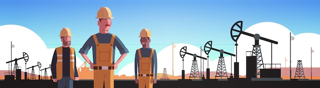 Workers in orange uniform working on oil drilling rig pumpjack petroleum production trade oil industry concept portrait horizontal