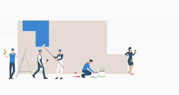 Рабочие красят стену в синий цвет баннера