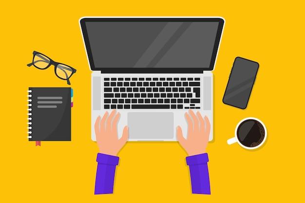 職場とラップトップでの作業。ノートパソコンとキーボードの手。ビジネス、管理、itのための職場。ノートパソコン、携帯電話、コーヒーマグ、ノートブック、メガネ。ラップトップで働くビジネスマン
