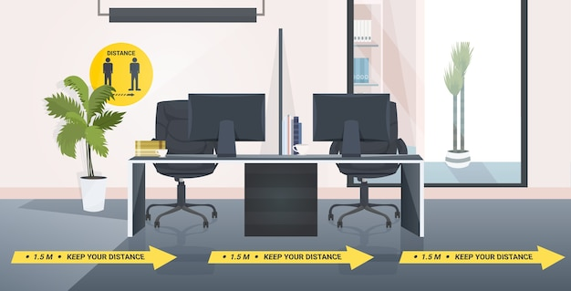 Workplace desk with signs for social distancing yellow stickers coronavirus epidemic protection measures