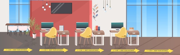 Workplace desks with signs for social distancing yellow stickers coronavirus epidemic protection measures