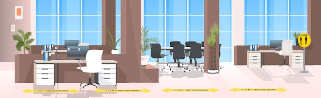 Workplace desks with yellow arrows signs for social distancing coronavirus epidemic protection