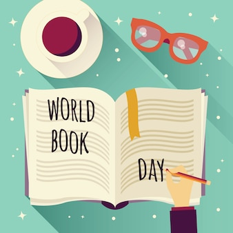 World book day, open book with a hand writing, coffee cup and glasses