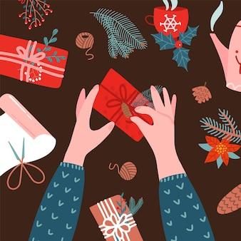 クリスマスプレゼントのラッピング。 2つの人間の手。装飾紙、プレゼントボックス、リボンの上面図