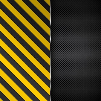 Yellow and black stripes on a perforated metal background
