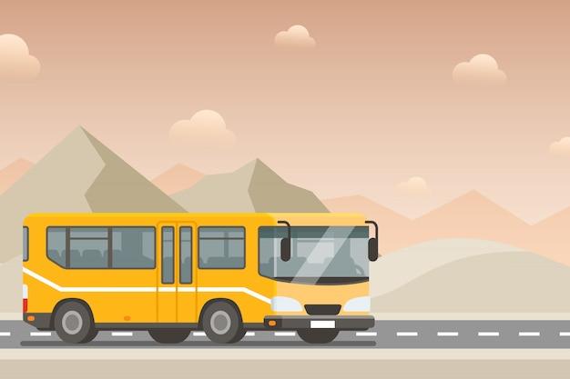 砂漠の高速道路を黄色いバスが行きます。
