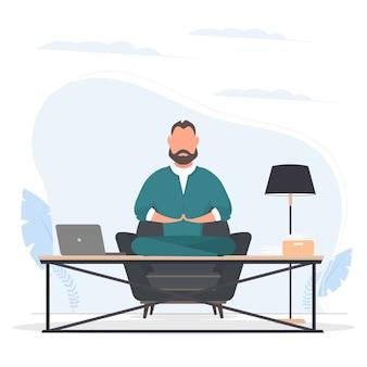 仕事でのヨガ。机の上のコンピューターとテーブルの上の蓮華座でリラックスしたビジネスマン。