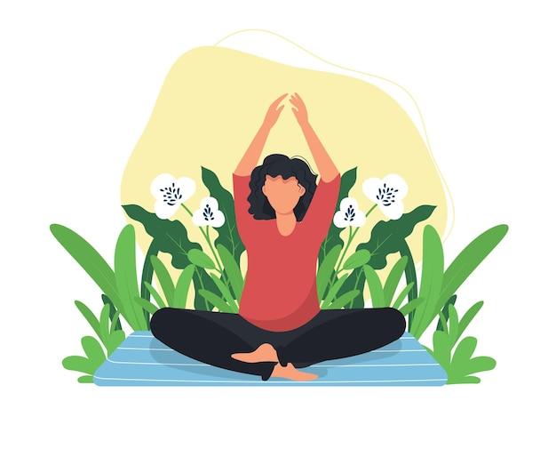 Йога медитируя женщина в зеленом лугу.