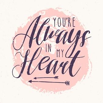 Надпись «ты всегда в моем сердце» или признание в любви, написанные каллиграфическим шрифтом на фоне розового круглого пятна краски на фоне